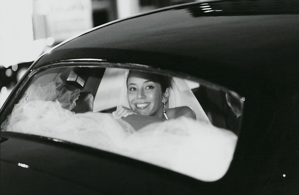Black and white photo of bride in black automobile