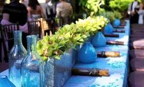 Tablecloth topped with blue motif and square vases