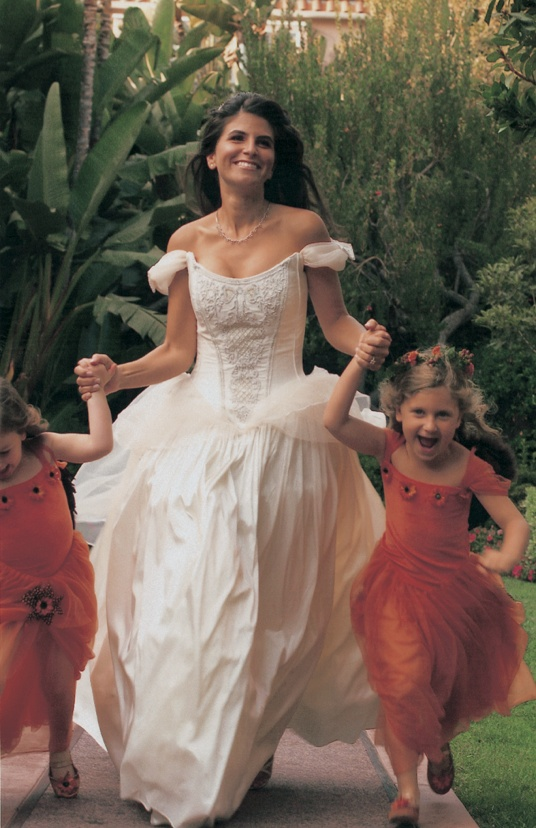 bride holds hands and runs with flower girls