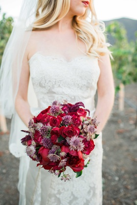 red purple pink bouquet flowers bride in jim hjelm dress red lips outside at vineyard