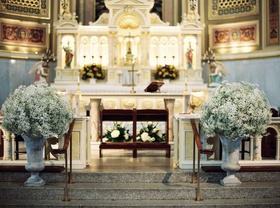Wedding ceremony Catholic church baby's breath in stone urns at altar stairs