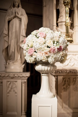 large blush and ivory floral arrangement in church with roses and hydrangeas