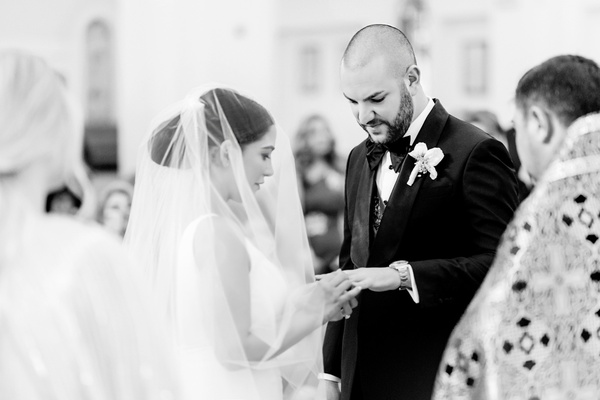 black and white photo of bride and groom exchanging rings during ceremony
