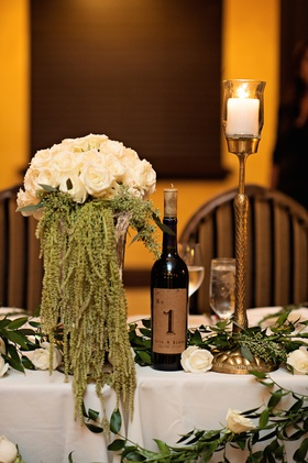 Head wedding table with white roses, green amaranthus, greenery, table number on wine bottle