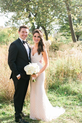 Bride in Naeem Khan wedding dress holding white bouquet with groom in tuxedo and bow tie outside
