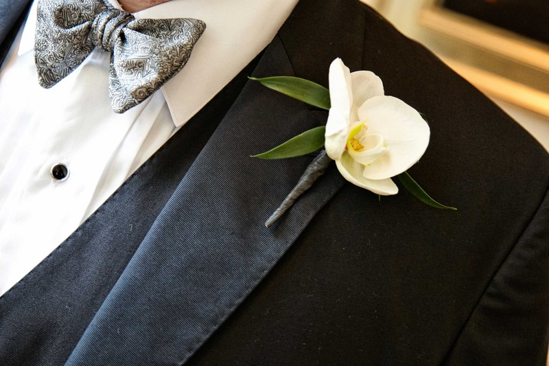 groom with white orchid boutonniere on a black suit jacket tux and gray detailed tie