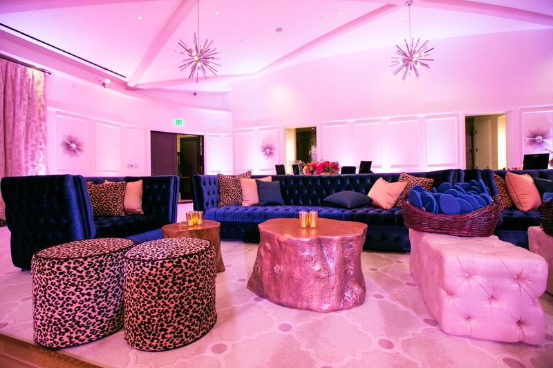 Pink lighting at wedding reception lounge area with blue velvet booths for dancing ballroom