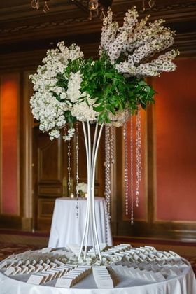 round escort card table flower petals in center tall centerpiece crystals white flowers greenery