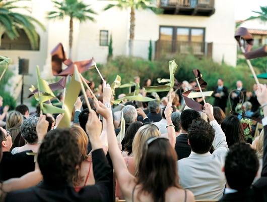 Guests wave ribbons in air after wedding ceremony