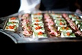 Server holding silver tray with two kinds of wedding appetizers with red toppings