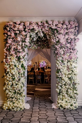 Wedding reception inspiration floral archway entrance to ballroom purple and pink white roses flower
