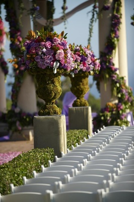 Outdoor wedding ceremony moss covered flower arrangement