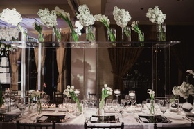 lucite table on top of wedding head table to display white flowers