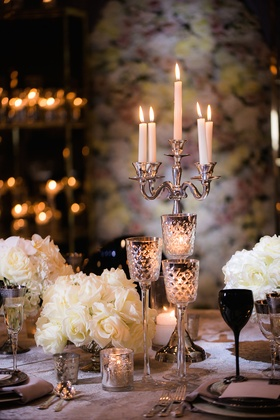 Wedding reception table with silver candelabra, stemmed mercury glass candleholders, white roses