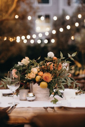 outdoor wedding reception bistro lights small centerpiece kumquats fresh fruit orange dahlia greens