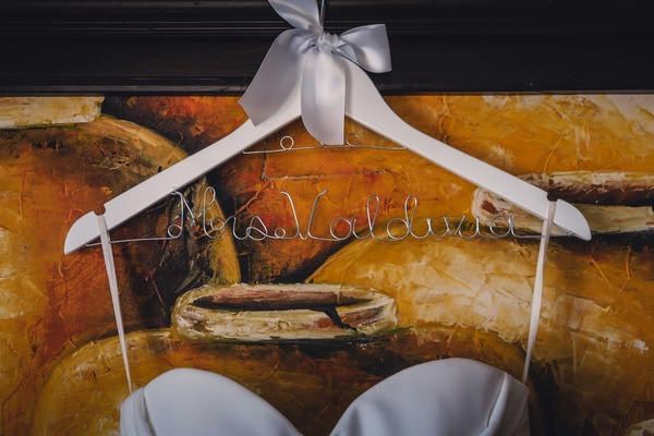 a hanger holding the brides white wedding dress that reads mrs valdivia