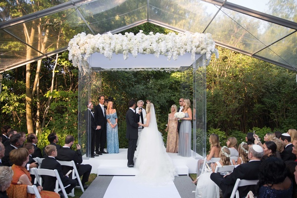 Bride and groom Jewish wedding outdoor clear glass tent venue orchid flowers greenery