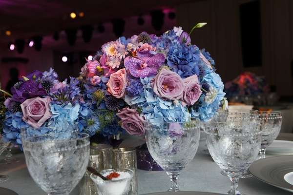 Whimsical garden themed wedding concept in shades of purple amp small floral arrangement with pink purple and blue on round white reception table mightylinksfo