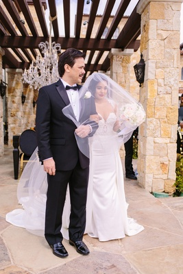 bride in riki dalal couture with long blusher veil stands with her father in a tux