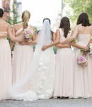 Pink bridesmaid dresses hugging each other from behind