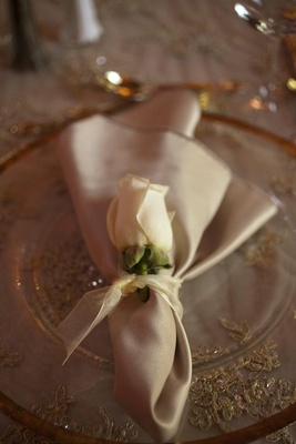 Wedding reception place setting with a clear gold-rimmed charger, gold napkin, and white rose