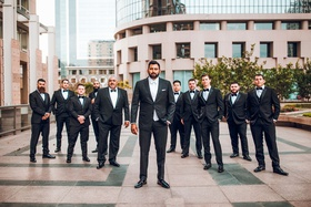 groom in suit with white bow tie and groomsmen in black bow ties outside downtown los angeles hotel