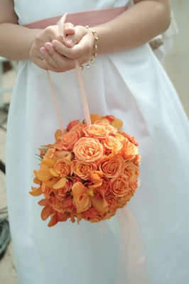 Flower girl's pomander bouquet of orange and yellow flowers