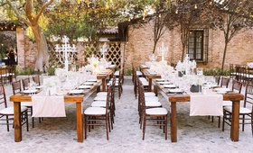 Outdoor wedding reception with wood tables, light pink sequined runners, candelabra