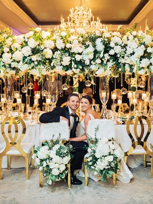 wedding reception elegant ballroom decor bride groom chairs white fur flower greenery gold guest