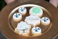 Frosted cookies served at wedding reception with bride's name, groom's initials, wedding cake