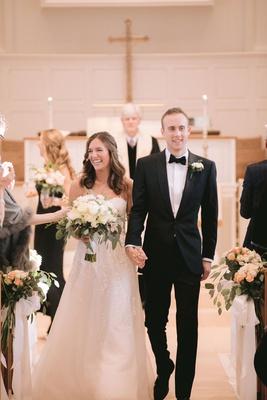 bride in strapless reem acra wedding dress neutral bouquet groom in tuxedo bow tie pastor cross