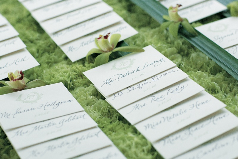 Wedding reception place cards on a bed of green flowers