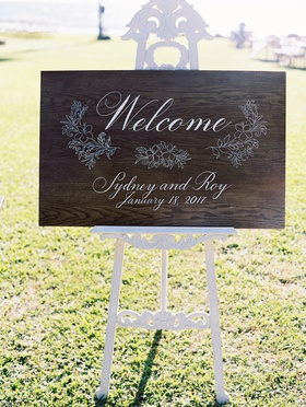wooden welcome sign for wedding ceremony on white stand