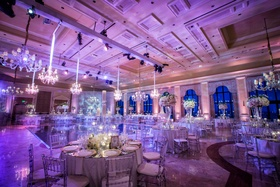 Wedding reception at The Breakers with purple lighting, chandeliers, high and low centerpieces