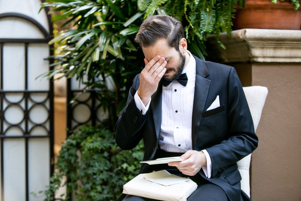 groom in tuxedo getting emotional hand on eyes face while reading love letter from bride