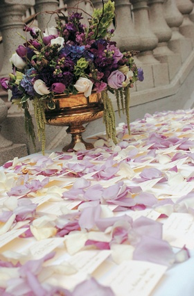 Escort cards on table sprinkled with flower petals and urn arrangement