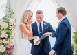 wedding ceremony bride touching eyes crying during vows groom officiant in blue suit vow book