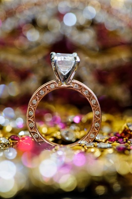 opulent engagement ring with large diamond and detailed band standing up around sparkling colors