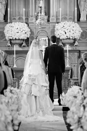 Black and white photo of bride and groom at end of church aisle