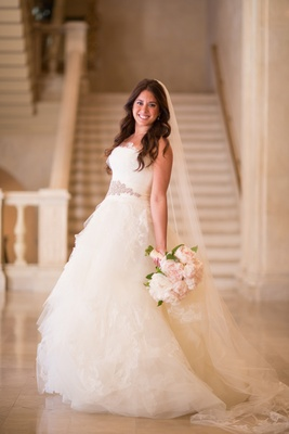 bride strikes a pose in a vera wang wedding dress with pink bouquet