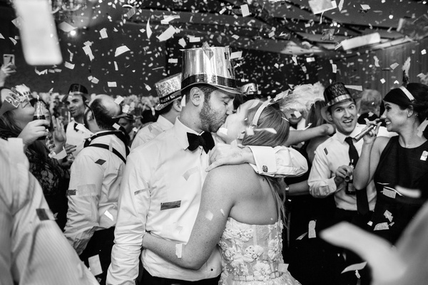 black and white photo of bride and groom in new year's eve hat and tiara wedding kiss confetti