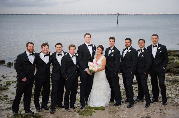 Bride and groom with men on beach bay in Florida