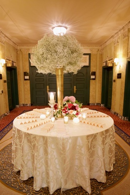 Tall gold vase on round escort card table filled with baby's breath and pink flower arrangements