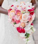cascading bouquet with pink, peach, orange, white roses, orchids, hot pink cockscomb celosia flowers