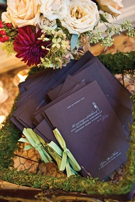 Wedding ceremony programs in moss chicken wire basket
