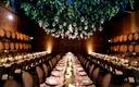 Green vine and grape chandelier in barrel room wedding reception