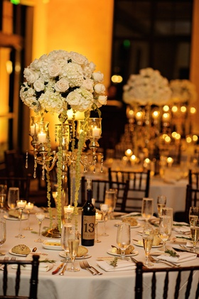 Wedding reception table with golden candelabra topped with white and green hydrangeas, white roses