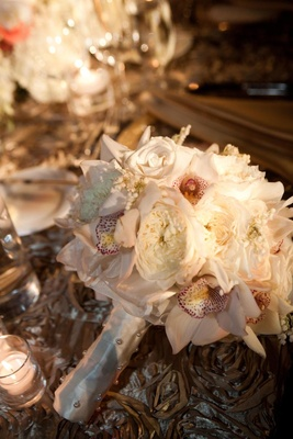 Wedding bouquet with rose and orchid flowers on reception table