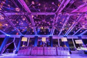 Custom chandeliers paired with a mirrored bar reflect off of a glass tent.