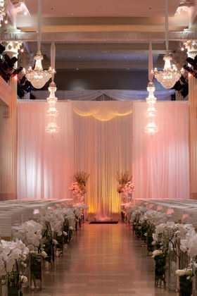 Crystal chandeliers above indoor ceremony with drapery